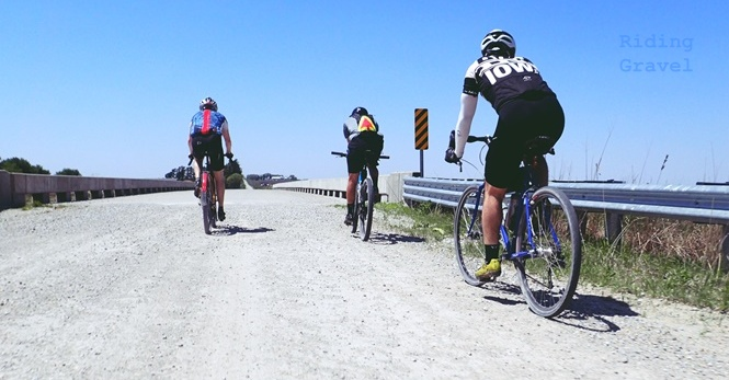 Three riders on a gravel road