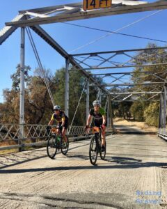 Two riders on a rural bridge