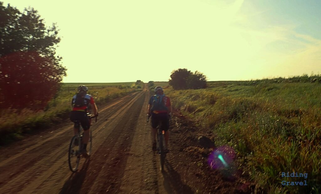 Two riders on a dirt road cycling.
